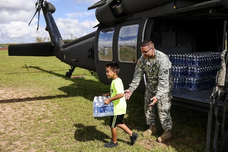 A Puerto Rico Army National Guardsman looks after a child carrying water in Orocovis, Puerto Rico, Sept. 29, 2017, while helping supply food and water to the community in Hurricane Maria's aftermath.