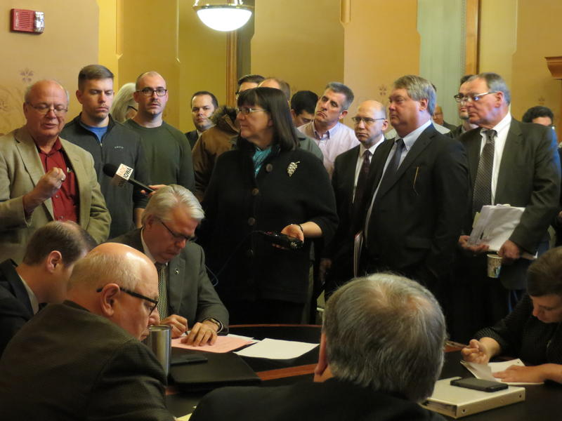 Supporters and opponents of a bill to revamp Iowa energy policy crowd into a statehouse committee room