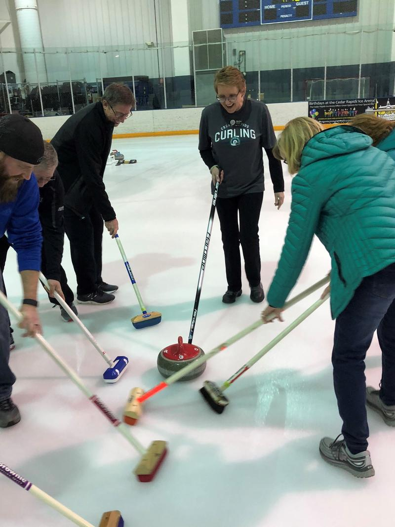 A team of new curlers practices sweeping with instructor Martha Marple.