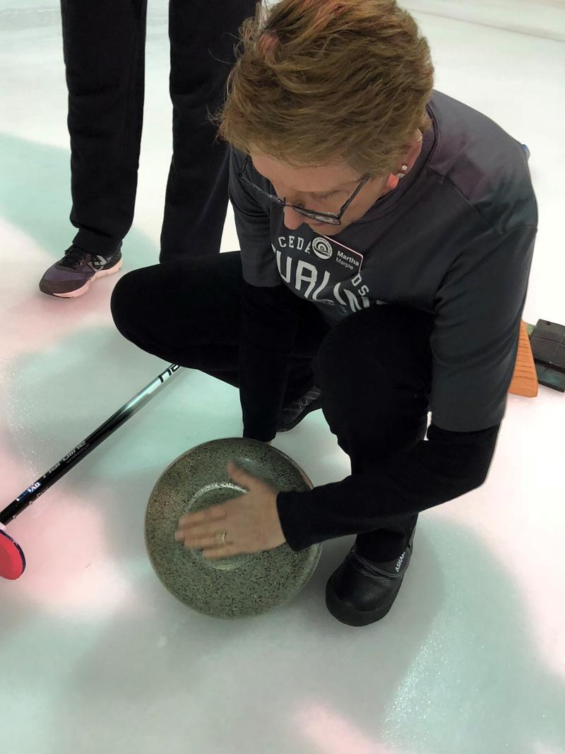 Instructor Martha Marple explains how a curling stone glides across the ice.