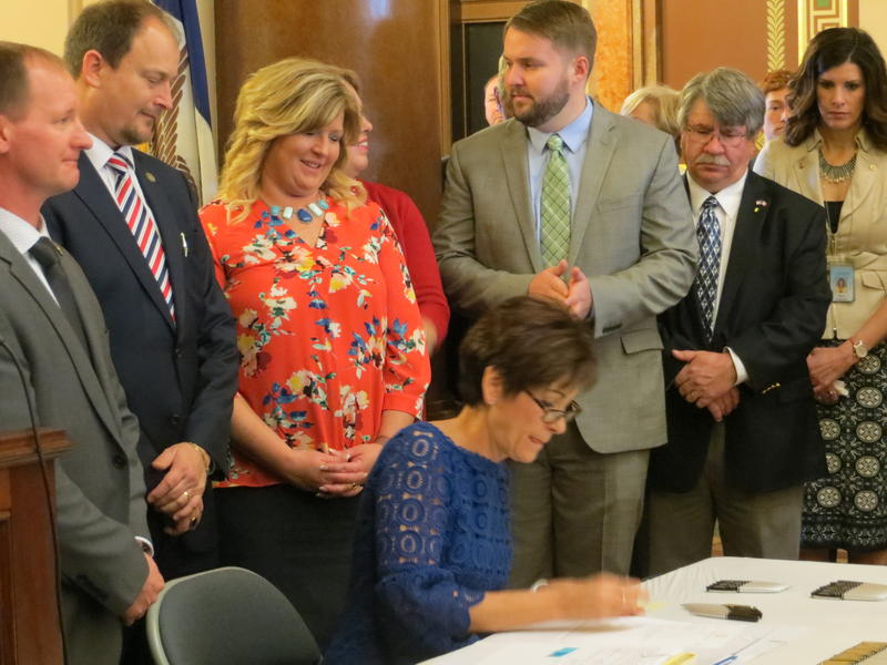 Gov. Kim Reynolds signs mental  health legislation into law, surrounded by legislators and advocates