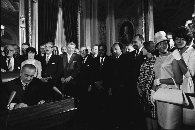 Two years before the Fair Housing Act, President Johnson signs the Voting Rights Act of 1965 while Martin Luther King, Jr. and others look on.