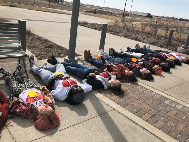 "High school students from Iowa City stage a ""die-in"" at the Brownells firearms retail store in Grinnell."