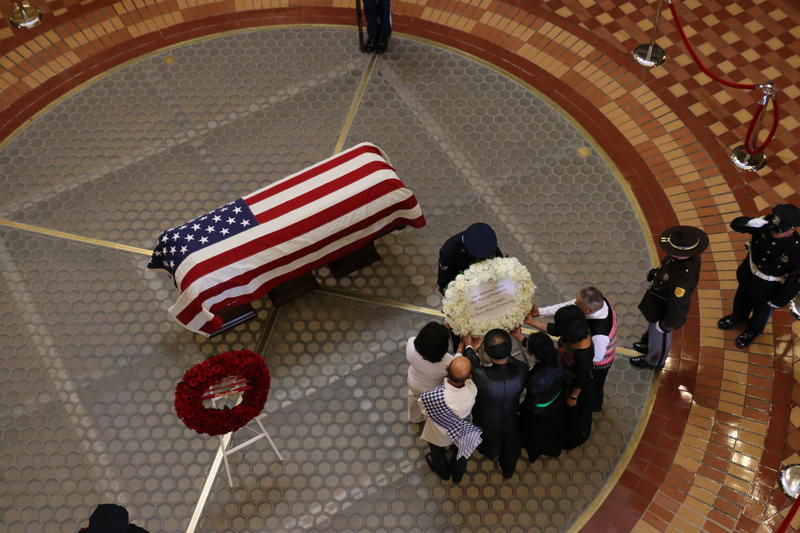 """Members of Iowa's Asian community help place a wreath by Gov. Ray's casket.  The wreath calls him, """"..our Ray of freedom."""""""