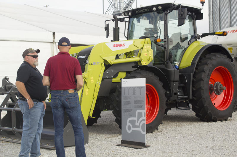 Jackson, Minnesota farmer John Peterson, left, and a friend from Germany stop at the CLAAS booth at the Farm Progress Show in Boone Tuesday.