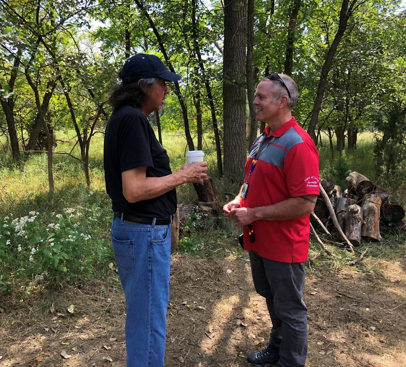 Frank LaMere (left), speaks with Will Meier on the grounds of the sweat lodge.