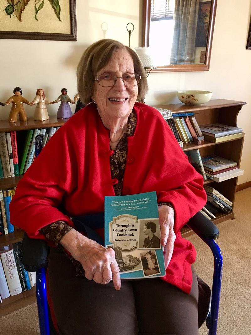 Evelyn Birkby holds up her latest book in her home in Sidney, Iowa.