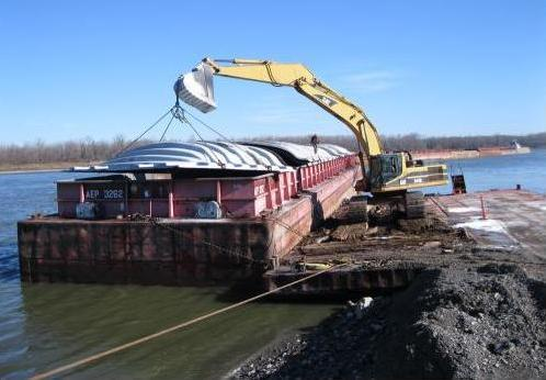 A backhoe places a cover on a barge near Cape Girardeau, Mo. The backhoe had just finished removing fertilizer that was shipped up the river from New Orleans.