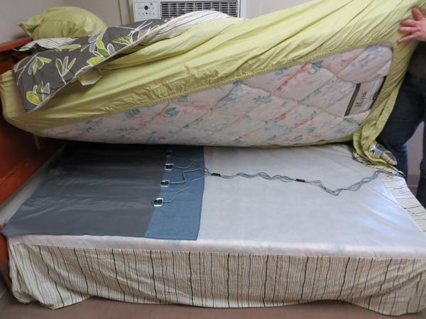 Water filled sensors placed under the mattress help monitor vital signs and restlessness