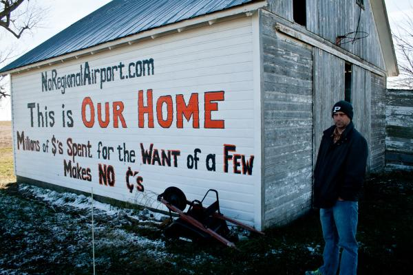Rob Hammann stands by a large shed on his property where his wife, Robin, has written a phrase protesting the regional airport.