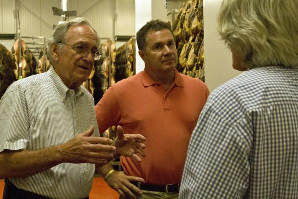 Congressman Bruce Braley (right), the Democratic candidate to replace Senator Tom Harkin (left), listen to the owner of La Quercia meat plant in Norwalk on August 3, 2014. The two lawmakers toured the facility and spoke to reporters about raising the minimum wage.