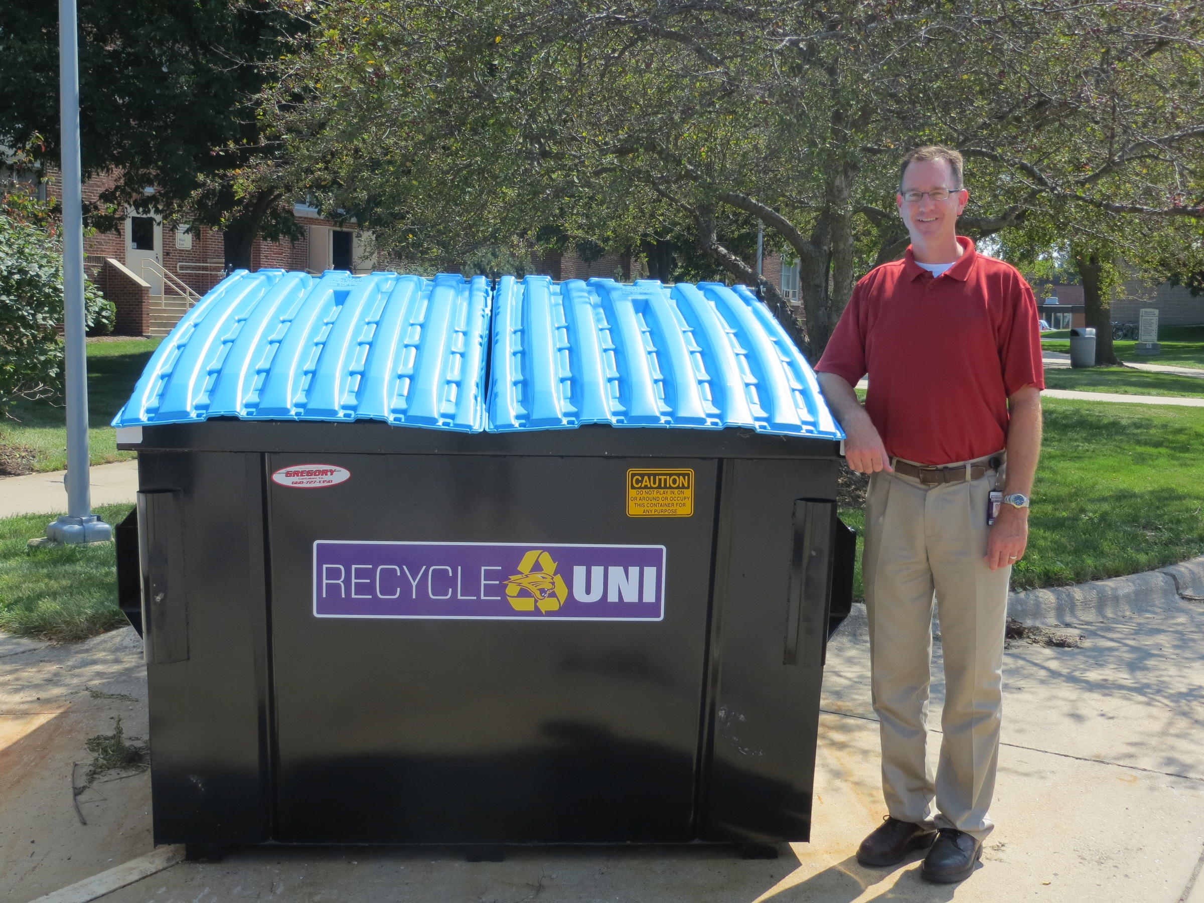 uni physical plant director mike zwanziger stands next to one the newly labled recycling dumpsters