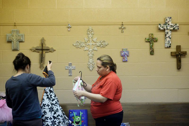 Volunteers Alex Vazquez, left, and Feliz Vazquez sort baby clothing Wednesday, March 18, 2015 at the Baby Room in St. Mark's Episcopal Church.