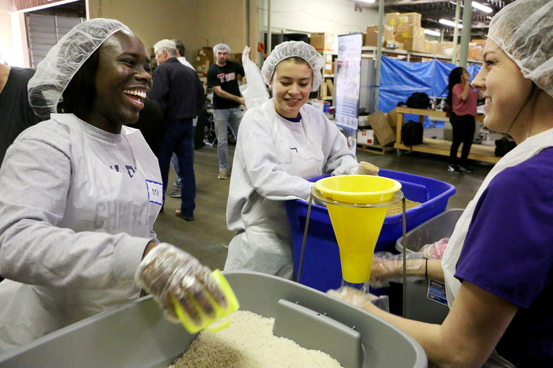 (Photo by Joy Bonala/KACU) ACU students from left, Deborah Badejo, left, Erika Reagan, and Bethany Miracle pack dehydrated fortified food during a packing event Monday, January 25, 2016 at the Global Samaritan Resources warehouse.