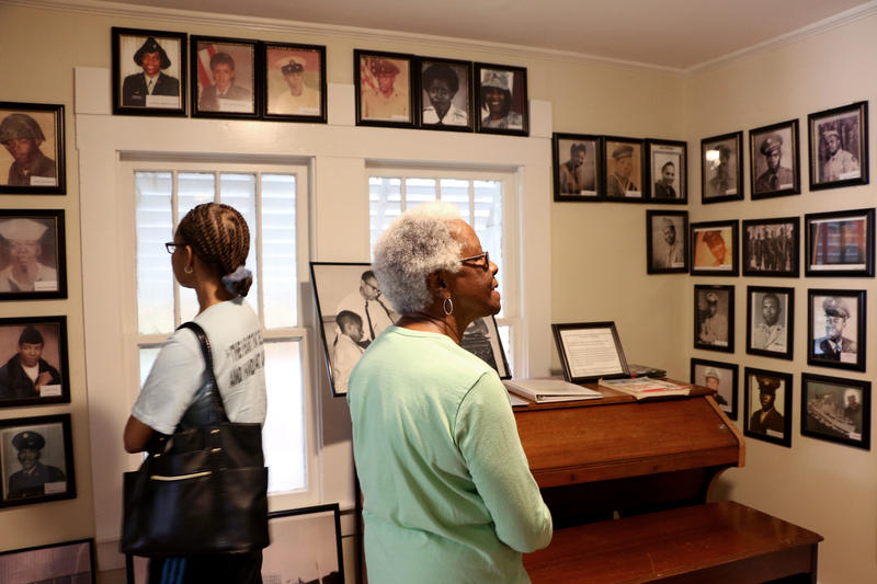 (Joy Bonala/KACU) Women browse through photographs of Taylor County African-American Service members.