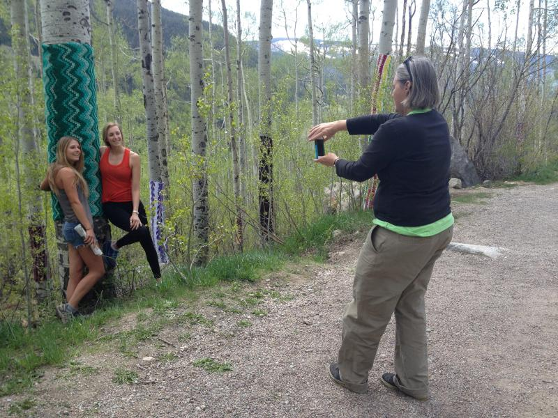 An artist responsible for a yarn bombing near Aspen takes a photo of two women who stopped to admire the afghans.