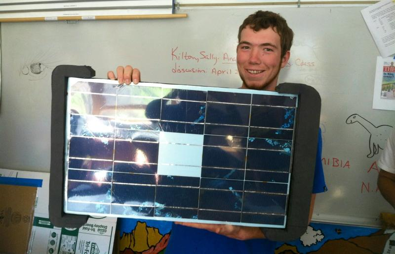 High School senior Tim Stephenson holds a solar panel he and his team put together. It's the roof of their solar remote controlled car.