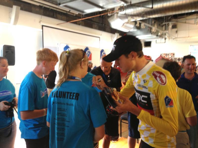2013 Pro Challenge winner and Aspen resident Tejay van Garderen signs a volunteer's t-shirt, after the ceremonies are over.