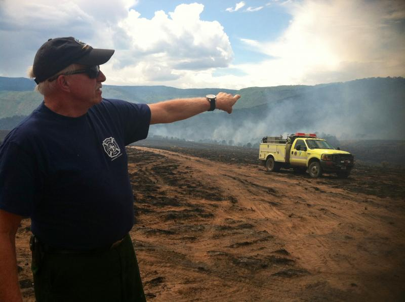 "Hank Van Berlo points to where the Red Canyon Fire is burning across from the firefighters' ""safe zone."""