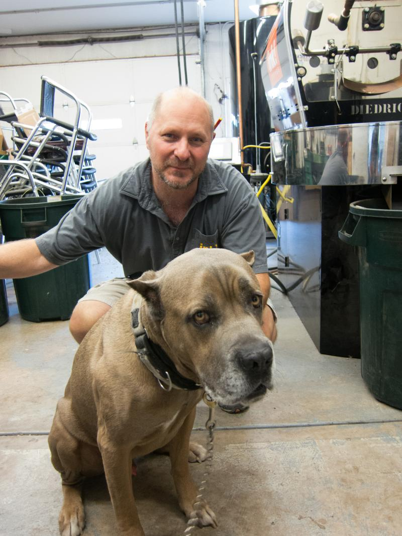 Ink Coffee roastmaster John Rose with his dog, Cocomo. Cocomo keeps Rose company while he's roasting.