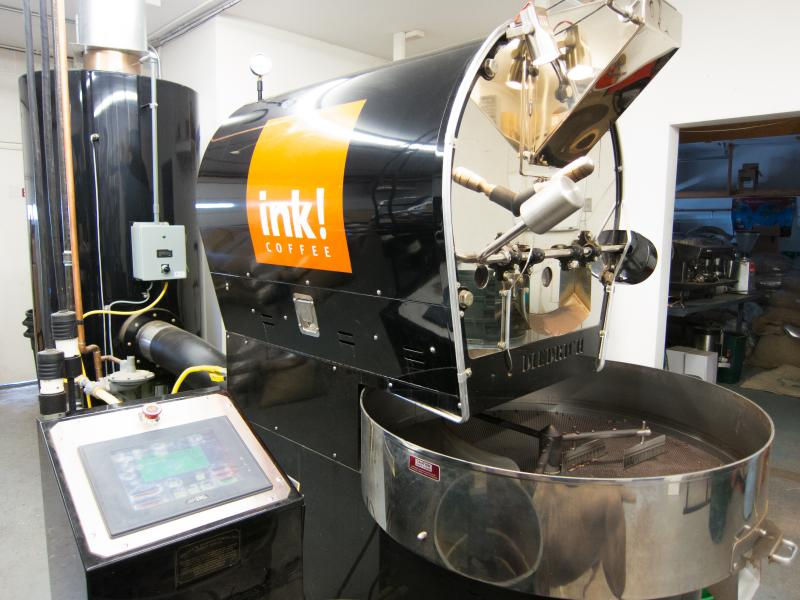 Green beans are poured into a hopper on top of the roaster. With the push of a lever, the beans will drop into the roaster where they'll tumble like clothes in a dryer.