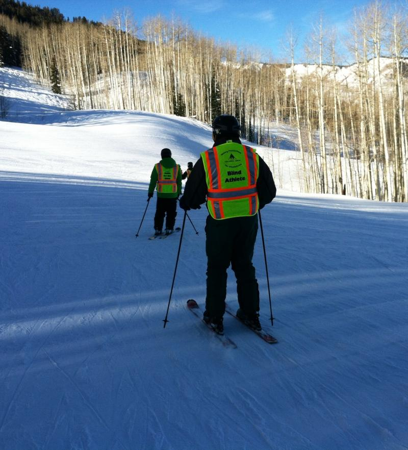 The visually impaired skiers and their guides wear bright clothing. For skier Michael Ward, the bright colors aid him in his skiing. He can more easily see his ski guide in front of him.