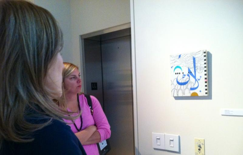 "Visitors to the exhibit examine the piece ""homage to kairouan."""