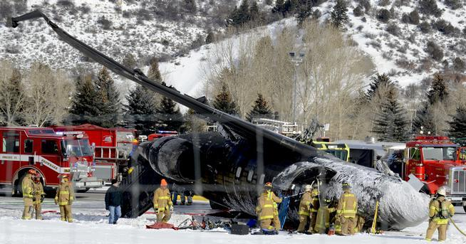 Emergency crews work near a passenger plane that crashed upon landing at the Aspen-Pitkin County Airport on Sunday.