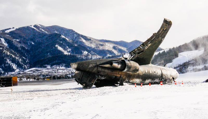 Charred fuselage of aircraft rests upside-down at East end of runway.