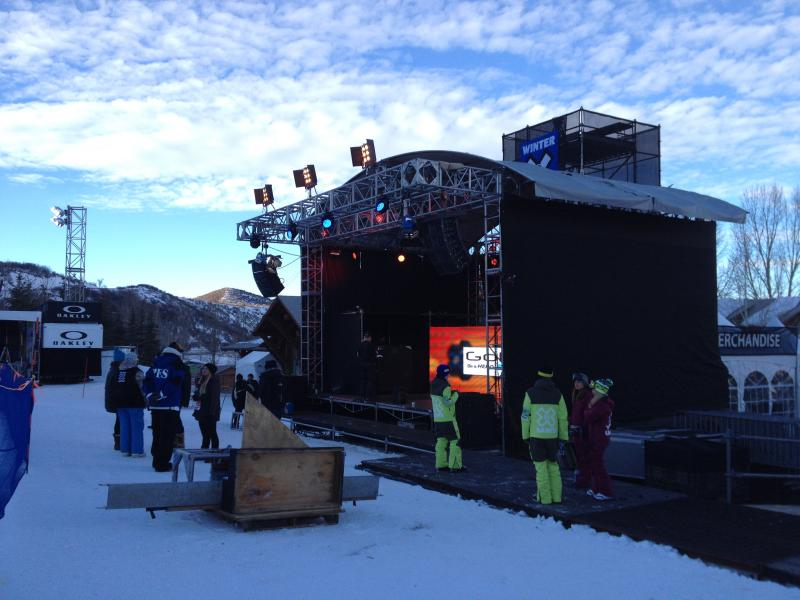 Workers and performers at a stage near the Superpipe.