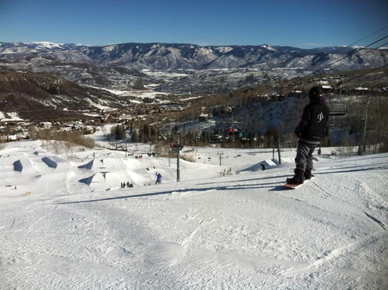 A snowboarders looks down on the terrain park at Snowmass Village.