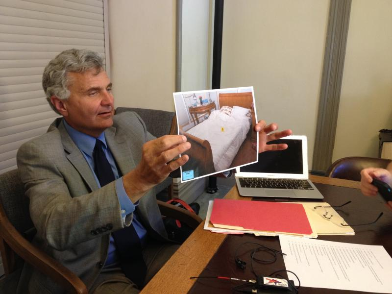 Attorney Greg Greer holds a photo of Nancy Pfister's bed, taken after her death.