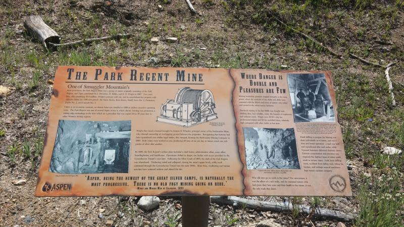 A recent sign about the Regent Mine helps to give context and history to the abandoned structures, piles.