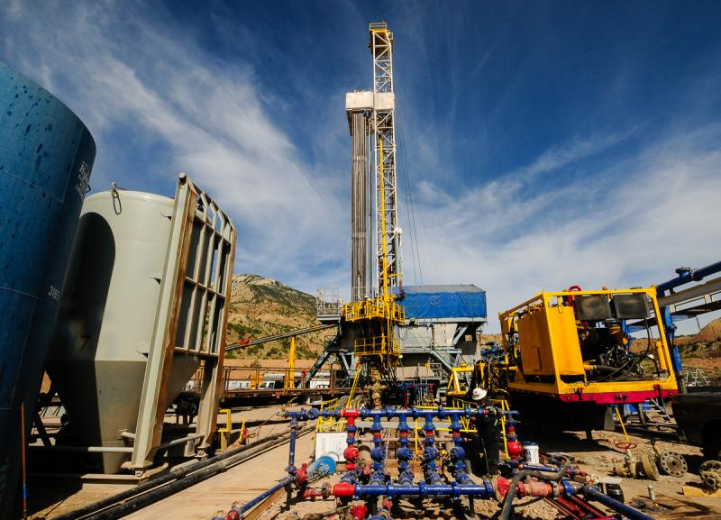 Two rigs, the H&P 318 drilling rig with white derrick, and a yellow snubbing rig drilling out plugs from a recently fracked well. There are 22 wells planned for this pad.