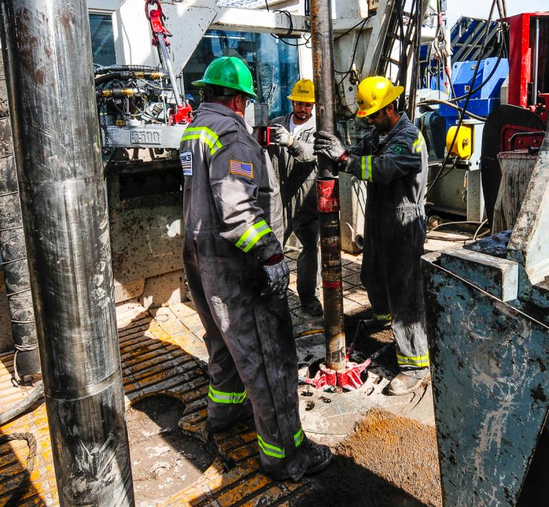 Drilling hands connecting well casing.
