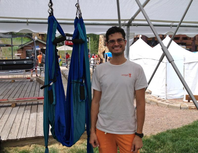 Gabriel Axel stands next to recycled parachute cloth used in suspension yoga.