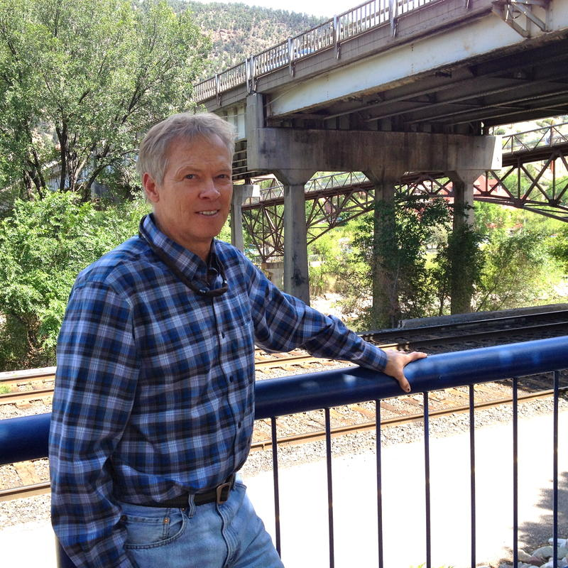 "CDOT Project Manager Joe Elsen stands in front of the existing bridge. Dark spots on the concrete ""legs"" behind are where concrete is stripping off."