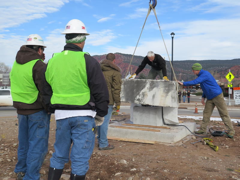 Construction workers look on as the marble platform is installed in the middle of the Highway 133 roundabout. The marble is from Marble, Colorado.