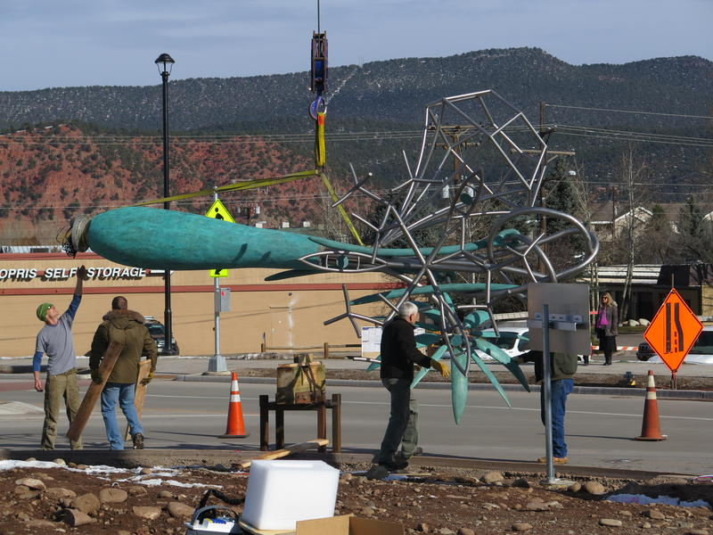 """The """"Sewing the Future"""" sculpture is turned on its side in preparation for its installation."""