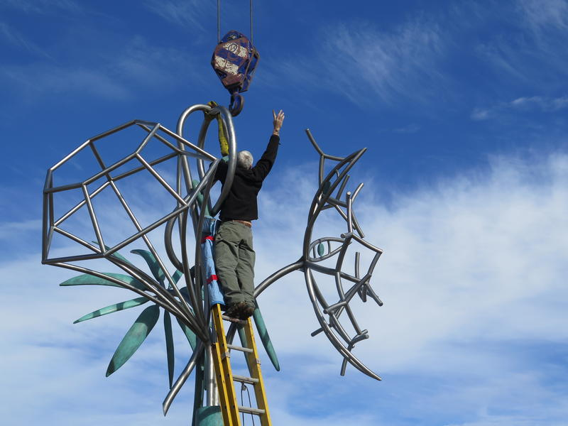 A member of the installation crew unhooks the crane from the top of the sculpture.