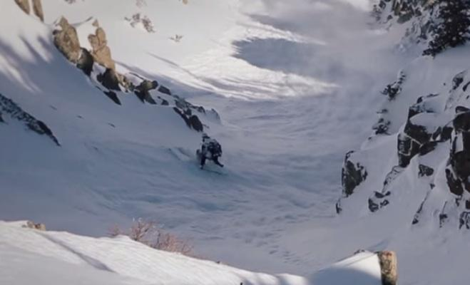 A skier narrowly escapes being swept away by an avalanche.