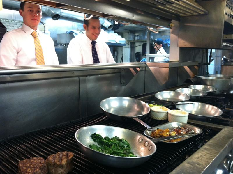 "The ""front of the house"" waitstaff take meals from the kitchen to people dining at Cache Cache."