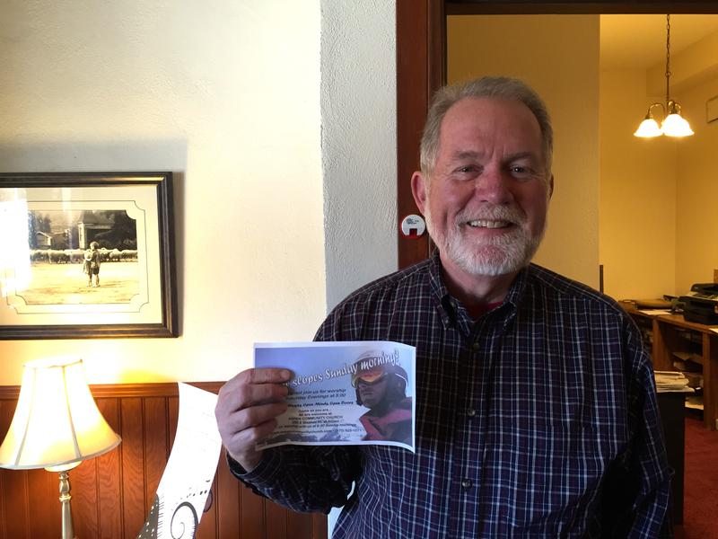 Pastor Mike Nickerson holds up information about weekly church services... held while skiing.