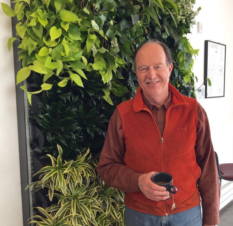 Michael Kinsley stands in front of the living wall in the new RMI lobby.