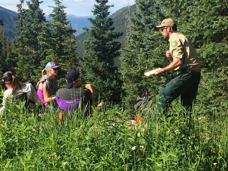 U.S. Forest Service Ranger Eric Tierney speaks with backpackers in Conundrum Valley.