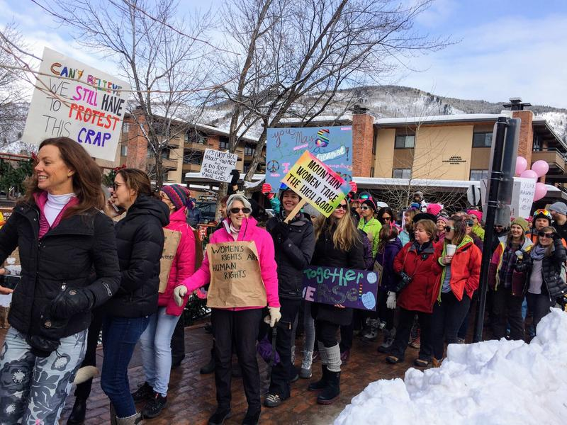 Women march from the gondola plaza through town.