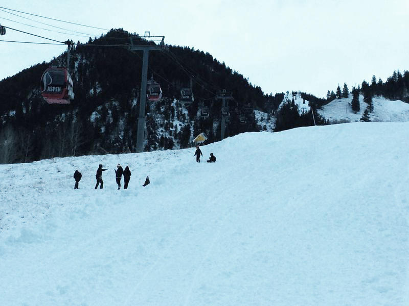 A group of visitors plays in the manmade snow at the base of Aspen Mountain.