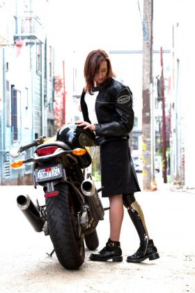 Deborah Bevilacqua poses in her black lace fairing by a motorcycle.