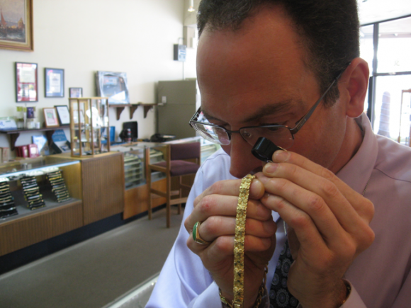 Jacob Notowitz examines a gold chain at Numis International.