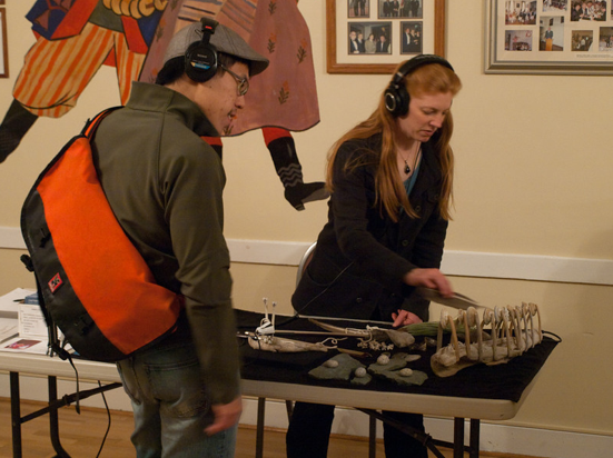Cheryl E. Leonard demonstrating shell and bone instruments from Antarctic. Crosscurrents Live, KALW Mission Arts and Performance Project, MAPP, December 2011. The Polish Club, 3040-22nd St., Mission district, San Francisco, California.